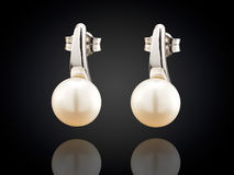 Golden earrings with pearl isolated on black background Royalty Free Stock Photos