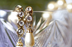 Golden earrings with pearls and rhinestones on crystal glass Royalty Free Stock Photo