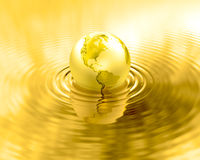 Golden Earth planet gold liquid ripples. Glossy gold world globe over water. Metal reflection and wave. Shiny wealthy earth. Luxury element Royalty Free Stock Images