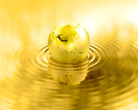 Golden Earth planet gold liquid ripples. Glossy gold world globe over water. Metal reflection and wave. Shiny wealthy earth. Luxury element Stock Image
