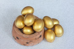 Golden easter egg in baked clay bowl Royalty Free Stock Photos