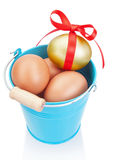 Golden easter egg in a blue bucket. Stock Photography