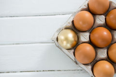Golden Easter egg with brown eggs in tray Stock Image