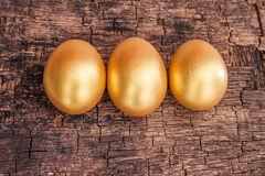 Golden easter egg on brown rough wooden board Royalty Free Stock Images