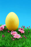 Golden easter egg on flower meadow & nice intensely blue sky Stock Photography