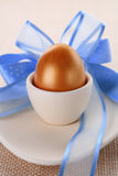 Golden Easter Egg In Beige Cup With Blue Bow Stock Photos