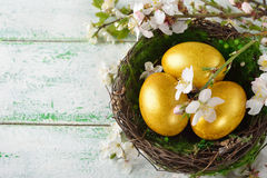 Golden easter egg in a nest. On a white background Royalty Free Stock Images