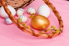 Golden Easter egg and pussy willow branch. Still life Easter decorative eggs and woven basket on colorful background close up Royalty Free Stock Photo