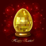 Golden Easter egg on a red blurry background Royalty Free Stock Images