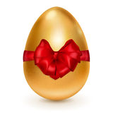 Golden Easter egg with red bow Royalty Free Stock Photography
