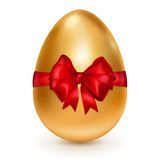 Golden Easter egg with red bow Royalty Free Stock Photos