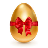 Golden Easter egg with red bow Royalty Free Stock Images