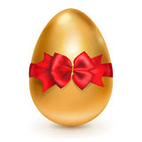 Golden Easter egg with red bow Stock Photography