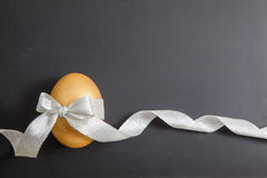 Golden easter egg with ribbon Stock Photos