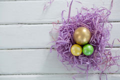 Golden Easter egg with two painted eggs in nest. Close-up of golden Easter egg with two painted eggs in nest Royalty Free Stock Photography
