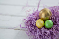 Golden Easter egg with two painted eggs in nest. Close-up of golden Easter egg with two painted eggs in nest Royalty Free Stock Photo
