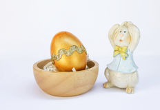 Golden Easter egg and wooden bunny Stock Image