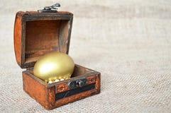 Golden Easter egg in wooden chest Stock Images