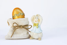 Golden Easter egg and wooden Easter bunny Stock Photos