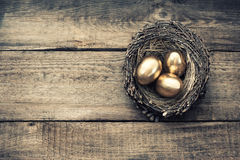 Golden easter eggs in birds nest vintage toned. Golden easter eggs in birds nest on wooden background. Vintage style toned picture Royalty Free Stock Image