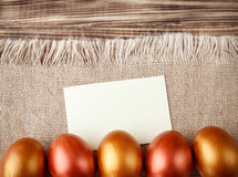 Golden Easter eggs on burlap. And wooden boards Stock Images