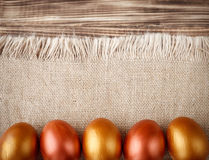 Golden Easter eggs on burlap. And wooden boards Royalty Free Stock Images