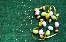 Golden Easter eggs and chickens on a green background royalty free stock photography