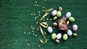 Golden Easter eggs and chocolate bunny on a green background stock photo