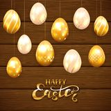 Golden Easter eggs on brown wooden background. Golden Easter eggs with decorative patterns and lettering Happy Easter on brown wooden background, illustration Royalty Free Stock Photography