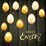 Happy Easter and golden eggs on black wooden background. Golden Easter eggs with decorative patterns and lettering Happy Easter on black wooden background Royalty Free Stock Photos