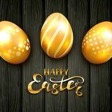 Golden Easter eggs with pattern on black wooden background. Golden Easter eggs with floral decorative patterns on black wooden background. Lettering Happy Easter Stock Photography