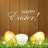 Golden Easter eggs in the grass on wooden background Royalty Free Stock Images