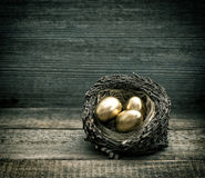 Golden easter eggs in nest over rustic wooden background Royalty Free Stock Image