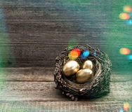 Golden easter eggs in nest. Retro style with light leaks Royalty Free Stock Photography