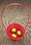 Golden Easter eggs in a red basket. Stock Photography