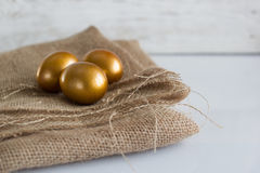 Golden easter eggs on white rustic background Royalty Free Stock Photography
