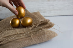 Golden easter eggs on white rustic background. Hand holding an egg Stock Images