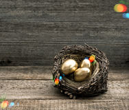 Golden easter eggs on wooden background with light leaks Stock Photos