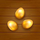 Golden Easter eggs on wooden background Stock Images