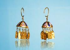 Golden Eastern Turkish vintage women`s handmade jewelry on a blue background.earrings, bracelets, rings, pendant. Female Golden Eastern Turkish vintage women`s Stock Photography