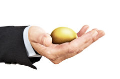 The golden egg. Man with formal suit holding in his hand golden egg. The golden egg is a metaphor representing income, profit, wealth, prosperity, chance Royalty Free Stock Photo