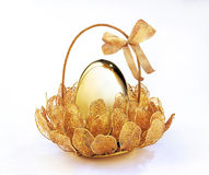 Golden egg. In basket isolated on white background royalty free stock photo