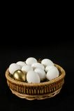 The Golden Egg. Basket with golden egg among white eggs royalty free stock photography