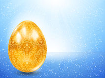 Golden egg on a background of blue rays. Royalty Free Stock Photo