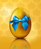 Golden egg with blue bow on vintage wallpaper  Royalty Free Stock Photos