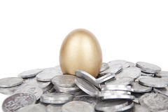Golden egg with coins. On white background Royalty Free Stock Images