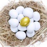 Golden egg in common nest. Golden egg on top of common white eggs inside a nest, isolated in white Stock Photo