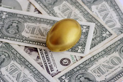 Golden egg on dollar currency Stock Photos