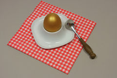 Golden egg in an egg cup on a red. Patterned napkin with spoon Stock Image