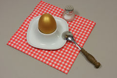 Golden egg in an egg cup. On a red patterned napkin with spoon and salt shaker Stock Photo
